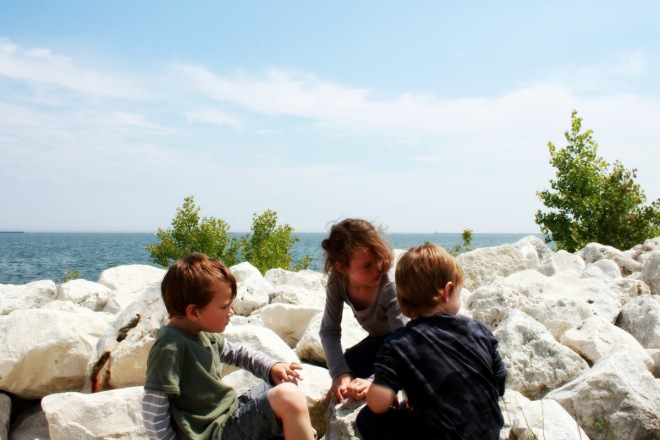 Three kids at the shoreline looking for treasures in the rocks