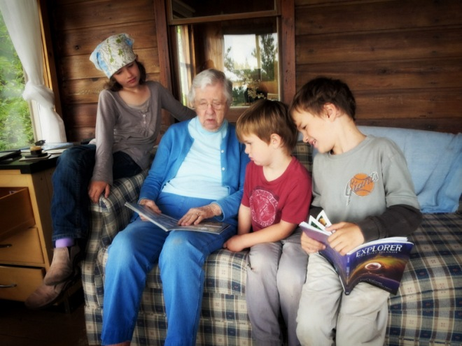 Grandma Smith reading to her great-grandchildren on the front porch