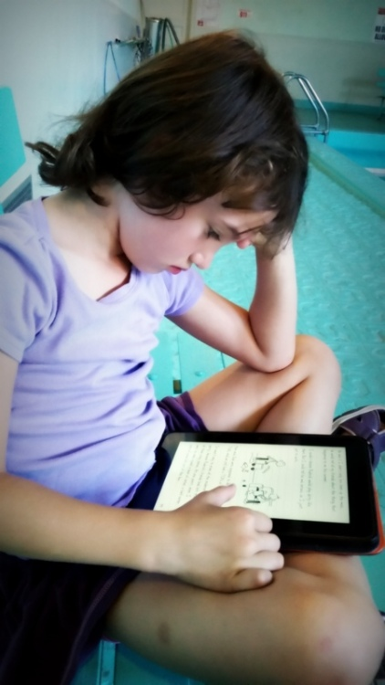 "Claire reading a ""Wimpy Kid"" book on my Kindle at swimming lessons"