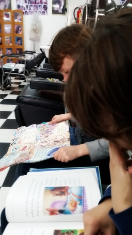 Soren took this picture of Claire and Ronin reading while waiting for hair cuts
