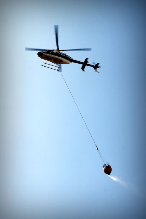 Helicopter dropping water on a fire