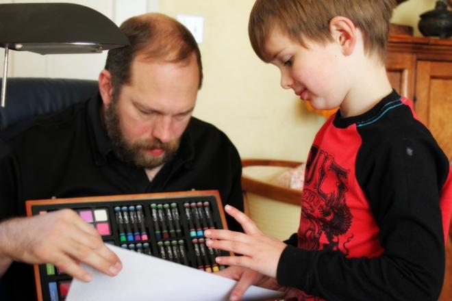 Soren showing off his art kit to Justin